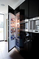 In the kitchen the large fridge is hidden behind black high-gloss parapan floor-to-ceiling cupboards