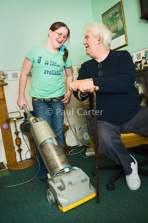 Young carers looking after elderly relatives.  Photo posed by models.  Model released...Young girl hoovers for her grandfather/ elderly relative...Following info from http://www.barnardos.org.uk :  .With so many adult responsibilities, young carers often miss out on opportunities that other children have to play and learn. Many struggle educationally and are often bullied for being 'odd'. They can become isolated, with no relief from the pressures at home, and no chance to enjoy a normal childhood. They are afraid to ask for help as they fear letting the family down or being taken into care..Facts and figures.othe average age of a young carer is 12..othe 2001 census shows that there are 175,000 young carers in the UK, 13,000 of whom care for more than 50 hours a week..omore than half of young carers live in one-parent families and almost a third care for someone with mental health problems.