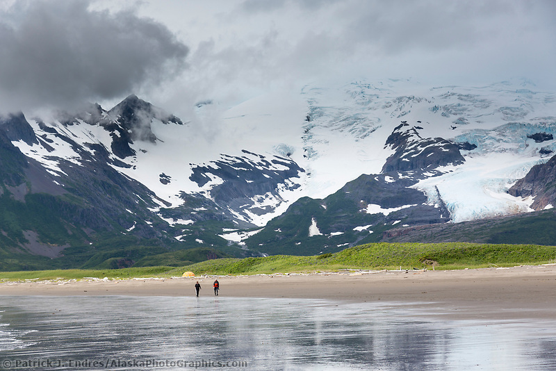 Hikers walk along the sandy beach on the coast of Katmai National Park, Alaska Peninsula, southwest Alaska.
