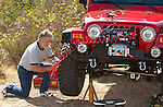 Changing a tire on a Jeep Wrangler in the field using a Warn Powerplant