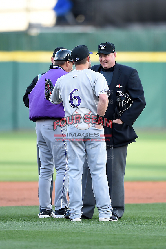 Louisville Bats outfielder Skip Schumaker (6) makes his point to home plate umpire Chad Whitson after being ejected by third base umpire Brian De Brauwere (background) with manager Jim Riggleman (jacket) during a game against the Buffalo Bisons on April 29, 2014 at Coca-Cola Field in Buffalo, New  York.  Buffalo defeated Louisville 4-1.  (Mike Janes/Four Seam Images)