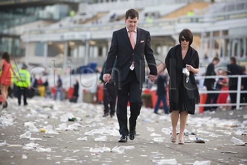 09.04.2011 The Grand National Festival day three. Grand National Day, Aintree. Two disappointed-looking race goers making their way out of Aintree stadium through piles of litter at the end of the final day of the three-day Grand National meeting.
