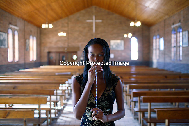 Dorah Mtetwa, age 22, an university student prays in the Catholic church.