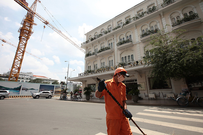 A street sweeper works outside the landmark colonial-era Hotel Continental in Ho Chi Minh City, Vietnam. July 4, 2011.