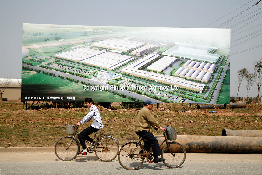 Two men bike past a billboard showing an artist impression of the Nanjing MG Automobile plant in Nanjing, China. The Chinese company is now in a position to take on Rover's assets and plan its future. It intended to relocate the engine plant and some car production plant to China but to retain some car production plant in the UK..27 Mar 2007