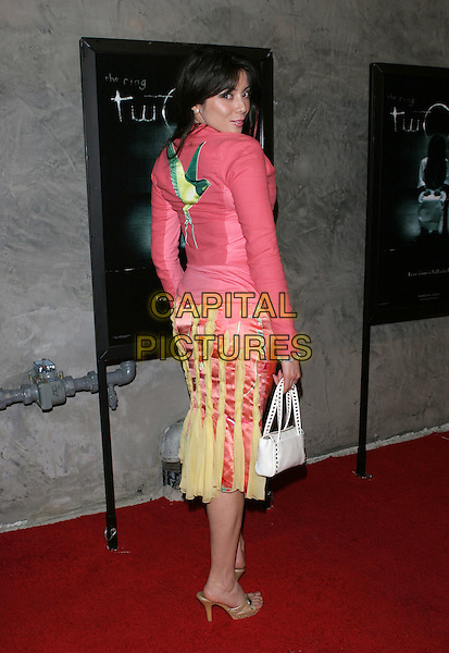 RACHEL GRANT.The The Ring Two Special Screening Party held at the Geisha Housel,  Hollywood, California.March 8th, 2005.Photo Credit: Jacqui Wong/AdMedia.full length pink embroidered jacket looking over shoulder back behind rear white purse stripes yellow and pink skirt.www.capitalpictures.com.sales@capitalpictures.com.© Capital Pictures.