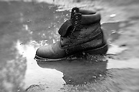 A boot was left behind in the middle of a muddy wet field...