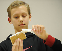 NWA Media/ANDY SHUPE - Zion Koch, 13, of Springdale, spreads icing on a graham cracker while making a gingerbread house-version of the Lincoln Memorial Saturday, Dec. 20, 2014, at the Springdale Public Library. Children were invited to make gingerbread houses and then decorate them with candy and icing.