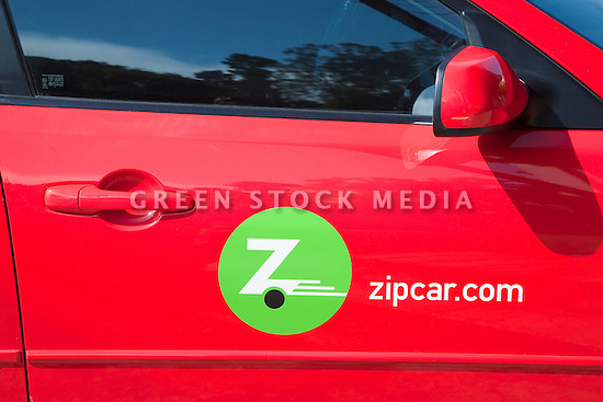 A close up of a Zipcar logo on a red car. Zip Car is a carsharing company whose customers pay by the hour or day. The company has dedicated parking spaces in cities. Bolinas, California, USA