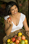 Hispanic woman with basket of fruit holding an apple