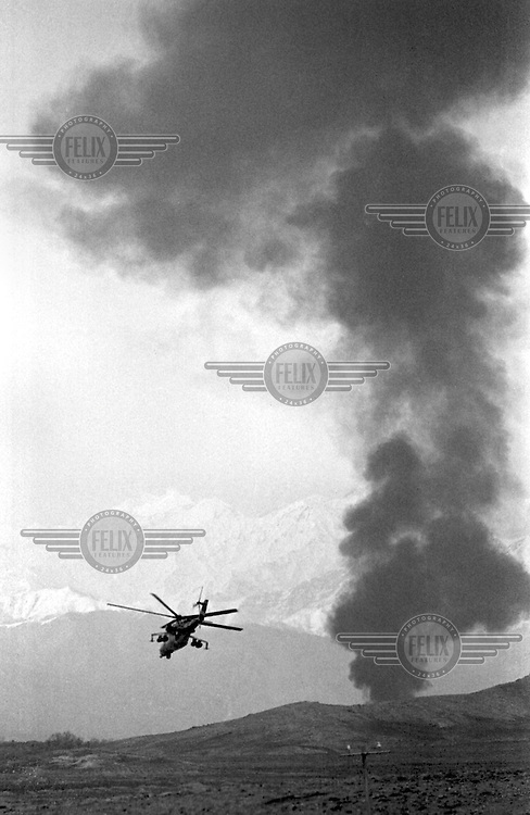 """A Soviet Mi-24 """"Hind"""" helicopter escorts a fuel convoy on its way to the Afghan capital Kabul on Sunday, February 5, 1989. Several of the fuel trucks were attacked and blown up by Mujahedeen fighters. Under siege for several years, the regime in Kabul depends heavily on Soviet military support."""