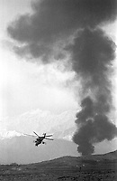 "A Soviet Mi-24 ""Hind"" helicopter escorts a fuel convoy on its way to the Afghan capital Kabul on Sunday, February 5, 1989. Several of the fuel trucks were attacked and blown up by Mujahedeen fighters. Under siege for several years, the regime in Kabul depends heavily on Soviet military support."