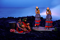 Hawaiian hula dancers performing by the lava entering the ocean