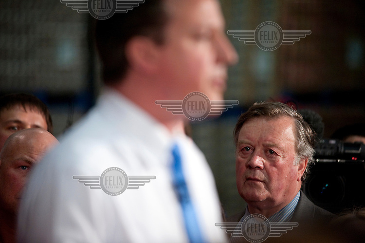 Conservative Party leader David Cameron, watched by former Chancellor Kenneth Clarke, takes questions from workers at a Coca Cola factory in Wakefield.