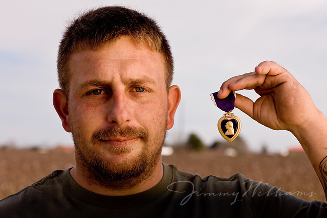 A veteran proudly shows his purple heart medal.