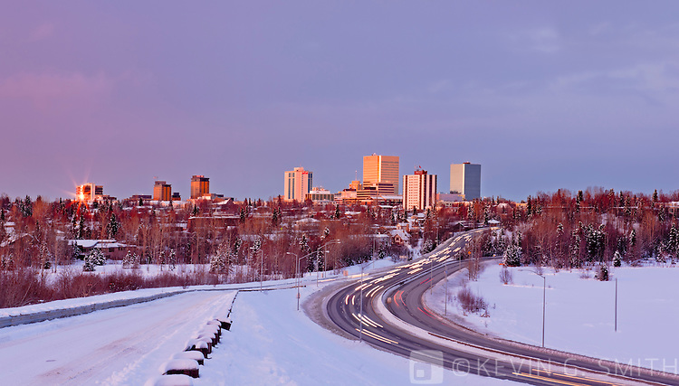 Winter sunset light falls on the downtown Anchorage Skyline overlooking Westchester Lagoon with traffic on Minnesota Blvd. composite image, Winter, Southcentral Alaska, USA.