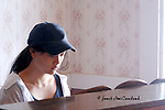 A lovely young Asian woman plays piano by the window light in the main lodge on Star Island, of the Isle of shoals, off the New Hampshire Coast. She is casually dressed in a base ball cap.