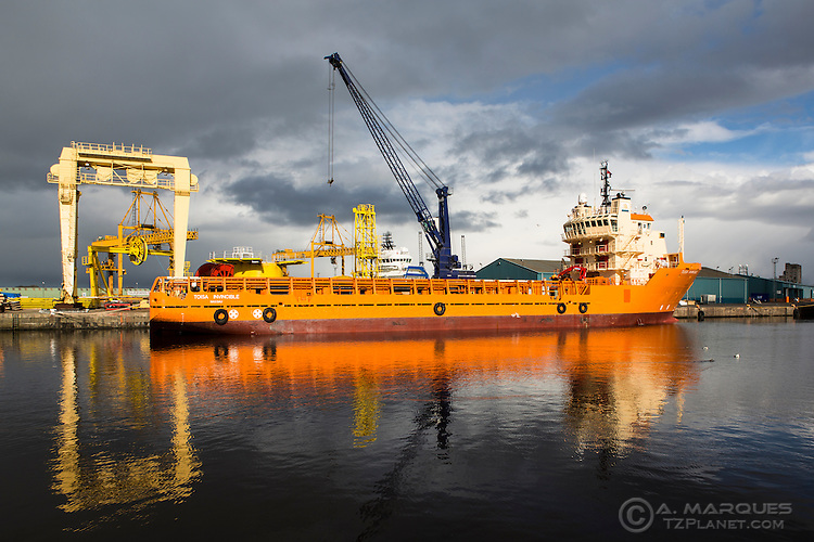 The ship Tosa Invincible docked at the Port of Leith, Edinburgh, Scotland.  .The Tosa Invincible is an offshore platform supply ship owned and managed by Sealion Shipping.  .The bright orange color of the ship contrasts well with the dark grey clouds and water.