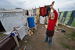 """A young woman refugee from Syria puts her laundry out to dry. She lives with her family in a rented """"tent""""--made from a billboard canvas--in the village of Jeb Jennine, in Lebanon's Bekaa Valley. They and other refugee families in the area are being assisted by International Orthodox Christian Charities and other members of the ACT Alliance.."""