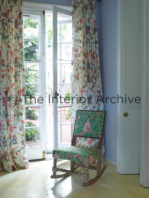 An arts and crafts style rocking chair upholstered in green floral chintz is placed in front of the French windows, which are also hung with curtains in a floral chintz fabric.