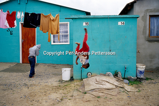 township,poverty,children,kids,water tap,laundry.Children play outside a house on June 17, 2004 in Khayelitsha, the biggest black township, about 20 miles outside Cape Town, South Africa. .©Per-Anders Pettersson/iAfrika Photos.......