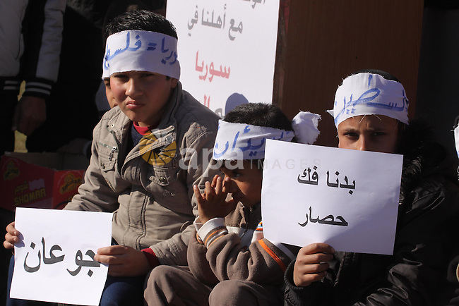 Palestinians take part in a solidarity with Palestinian children at Yarmouk refugee camp in Syria in Gaza city on January 8, 2014. The Syrian army has besieged the Yarmouk Palestinian camp for a year as battles rage inside the sprawling suburb in southern Damascus almost daily between rebels and pro-regime fighters. Photo by Mohammed Asad