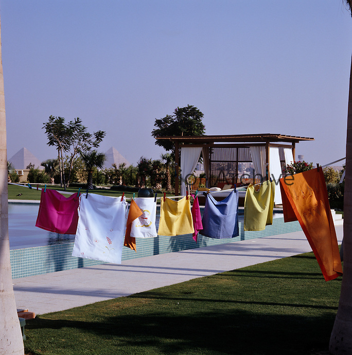 Strung between two palm trees a row of brightly coloured linen dries in the strong Egyptian sun