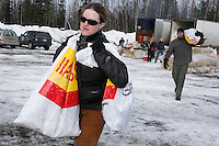 Saturday February 20, 2010.   Volunteers carry musher food bags to waiting Iditarod airforce planes for delivery to the Rainy Pass checkpoint at Willow Airport.