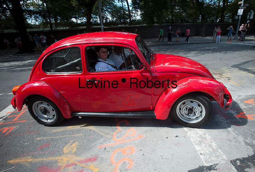 A cherry red restored classic Volkswagon beetle turns a corner on Fifth Avenue in Manhattan in New York on Saturday, September 14, 2012.  (© Richard B. Levine)