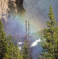 A rainbow glows before a large waterfall in the Beartooth Wilderness.