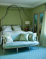 The bedroom is decorated in shades of eau de nil and pale blue; a wrought-iron four poster bed takes centre stage, an antique settee is set at the foot of the bed.