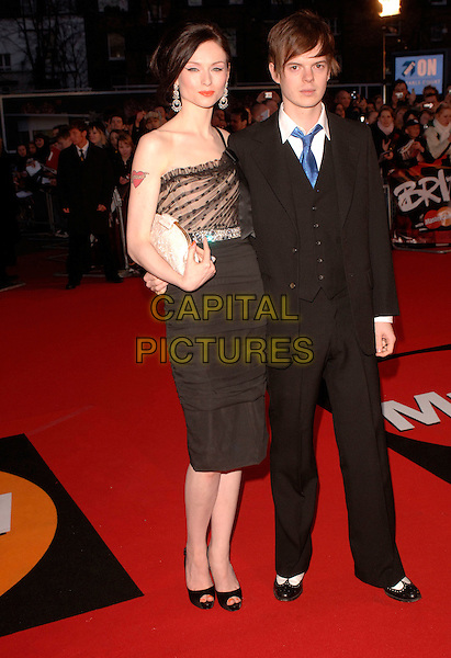 """SOPHIE ELLIS BEXTOR & RICHARD JONES.Arriving at the 2007 """"Brit Awards"""" at Earls Court, London, England, 14th February 2007..full length black dress one shoulder strap couple married husband wife heart tattoo.CAP/FIN.©Steve Finn/Capital Pictures."""