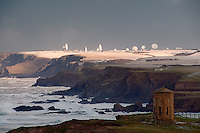Dramatic light on the snow covered downs and satellite dishes at.GCHQ Bude as the swell of a big Atlantic storm pounds the coast. In the foreground lies the Temple of the Winds, on Compass Point, built by wealthy local landowners the Acland family in 1840.