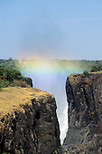 Victoria Falls, Zambia to Zimbabwe border. The Falls through a cleft in the rocks with rainbow.