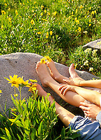2 generations of feet with daisies between toes outdoors in daisy field