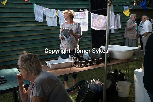 Ebernoe Horn Fair West Sussex UK.  Tea tent lady washing and drying dishes. 2015