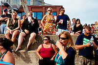 Spectators gather on the beach to watch Siene boat races and the Greasy Pole Contest at St. Peter's Fiesta in Gloucester, Massachusetts, USA.
