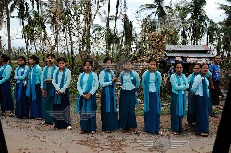 The women's organisation of the Union Solidarity and Development Association (USDA, a civilian wing of the military junta) line up to greet a visitiing government VIP before food aid is handed out to victims of Cyclone Nargis, which hit Burma on 02/05/2008. Near Tantwye, Ayeyarwaddy Division.