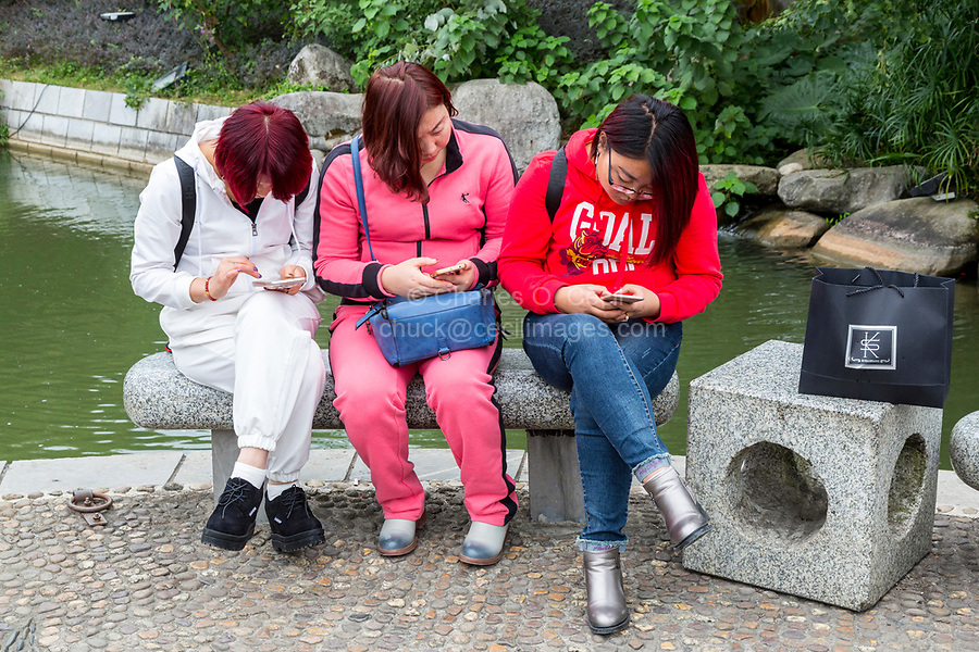 Guilin, China.  Three Chinese Women Checking their Cell Phones.