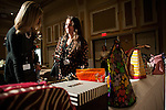 "Samantha Tischler (right) and Brittany Mclintire (left) talk about the selection of purses availible at the ""Power of the Purse"" silent  auction during the Women in Philanthropy conference on Thursday, March 14th in Baker Ballroom. Photo by: Ross Brinkerhoff."
