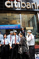 Security guards outside the Citibank in Central District of Hong Kong, preventing the protesters who lost money in the financial crisis through bad investements linked to Lehman Brothers from going inside the bank..
