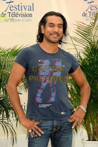 "NAVEEN ANDREWS.Photocall promoting the television series ""Lost"" on the fourth day of the 2008 Monte Carlo Television Festival held at Grimaldi Forum, Monaco, Principality of Monaco..June 11th, 2008.half length hands on hips blue t-shirt stubble facial hair .CAP/TTL .© TTL/Capital Pictures"