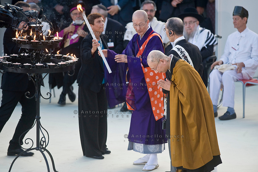 Assisi,Italy, September 20, 2016. From left; Supreme Advisor of Tendai Buddhist Denomination Sugitani Gijun, Nichiko Niwano of Rissho Kosei Kai, and Buddhist Monk Minegishi Shoten walk to light a candle during the closing event of an inter-religious prayer gathering, in front of the Basilica of St. Francis, Assisi. War refugees and leaders and representatives of several religions, including Christians, Jews, Muslims, Hindus and others, joined Pope Francis in a day of prayer for peace in Assisi, the hometown of St. Francis, who preached tolerance and gentleness.
