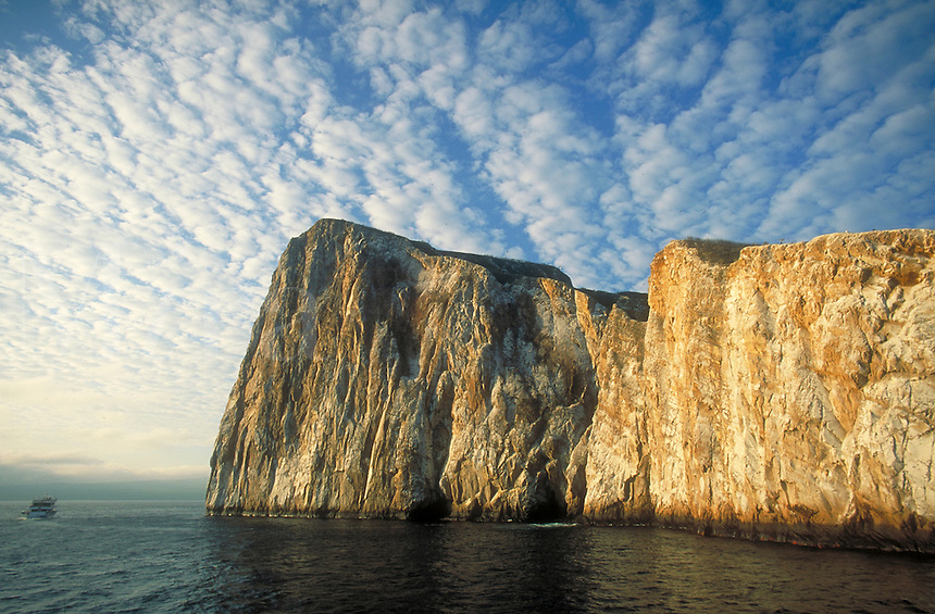 Tourist boat cruises along the steep rock slope of Kicker Rock near San Cristobal Island, cloud formations, clouds, cliffs. Kicker Rock (Sleeping Lion Rock) Galapagos Islands Ecuador Pacific Ocean, 650 miles west of South America.