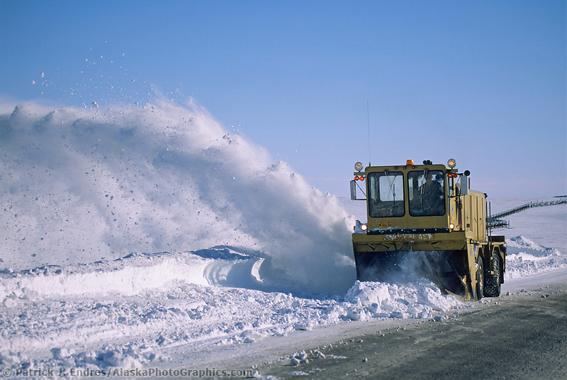 High winds blow drifting snow across the James Dalton Highway north of the Brooks Mountain Range, on Alaska's Arctic Coastal Plains. Alaska dept. of transportation removes snow drifts with blower.