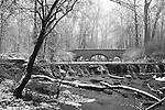Snow Covered Trees Framing A Stone Bridge And Waterfall During Winter In The Park, Black And White, Sharon Woods, Southwestern Ohio, USA