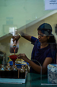 A worker pours ayurvedic treatment oil at the dispensary of the National Research Institute of Panchakarma in Cheruthuruthy in Thissur district of Kerala, India.