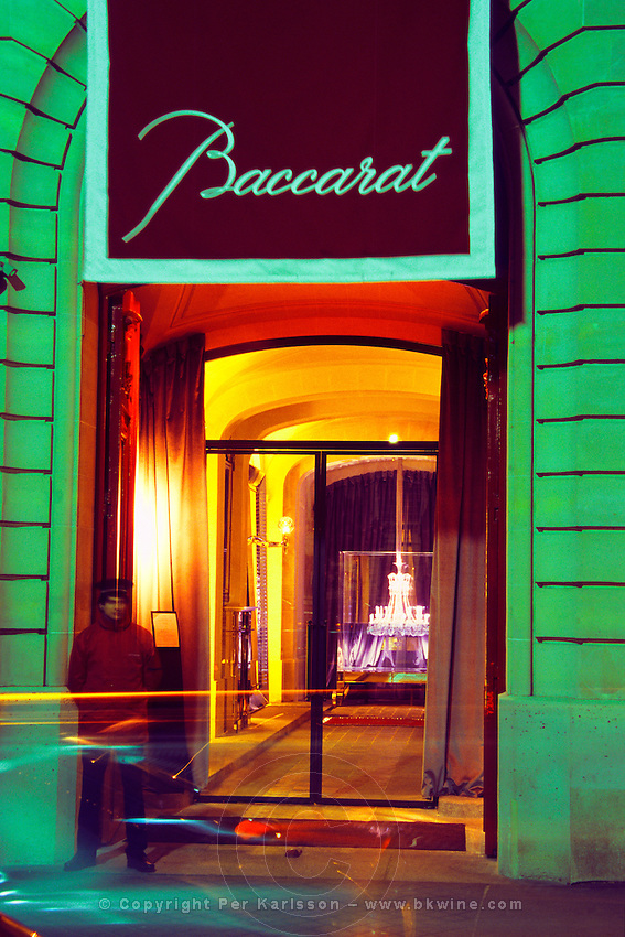 The entrance with a parking attendant, guests arriving in cars, the giant crystal chandelier in an aquarium inside. At The Baccarat museum, shop, restaurant at the Hotel de Noailles in Paris. Designed by Philippe Starck. The entrance of the Baccarat Museum with a parking valet and guest arriving. Inside is the aquarium with the crystal chandelier