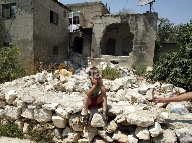 A Palestinian child sits in front of her house which damaged by the armed jewish settlers  in sheikh Jarah east of Jerusalem on July 9, 2009.  Photo by Mahfuz Abu Turk