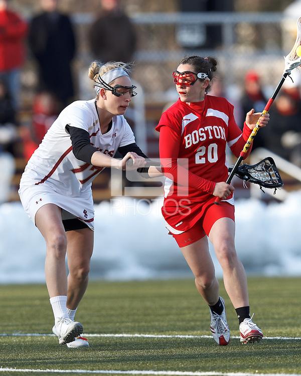 Boston University midfielder Sydney Godett (20) on the attack as Boston College midfielder Mikaela Rix (17) defends..Boston College (white) defeated Boston University (red), 12-9, on the Newton Campus Lacrosse Field at Boston College, on March 20, 2013.